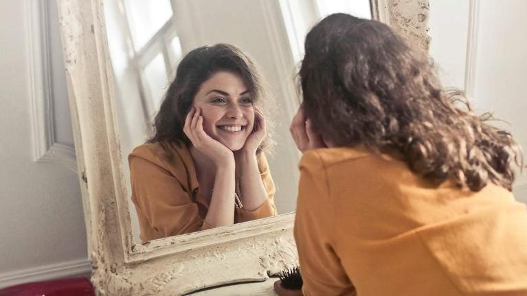 a woman looks at herself in the mirror | invisalign bondi junction